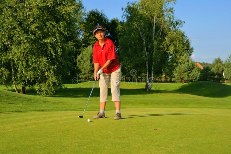 Сыграйте в гольф, игрок в гольф женщины толкая шарик в отверстие стоковые фото