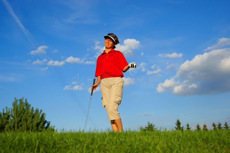 Сыграйте в гольф, смеющся над игроком в гольф женщины, с ручкой и шариком в его руке стоковое изображение rf