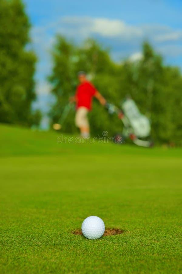 Сыграйте в гольф, шарик лежа на зеленом цвете рядом с отверстием, на заднем плане пойдите игрок в гольф стоковые изображения rf