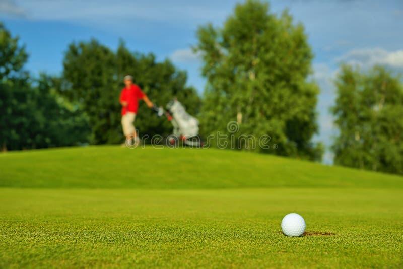 Сыграйте в гольф, шарик лежа на зеленом цвете рядом с отверстием, на заднем плане пойдите игрок в гольф стоковые фото