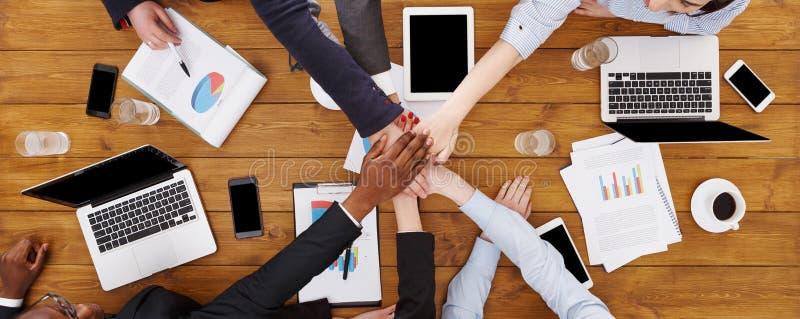 Сыгранность и teambuilding концепция в офисе, людях соединяют руку стоковое фото