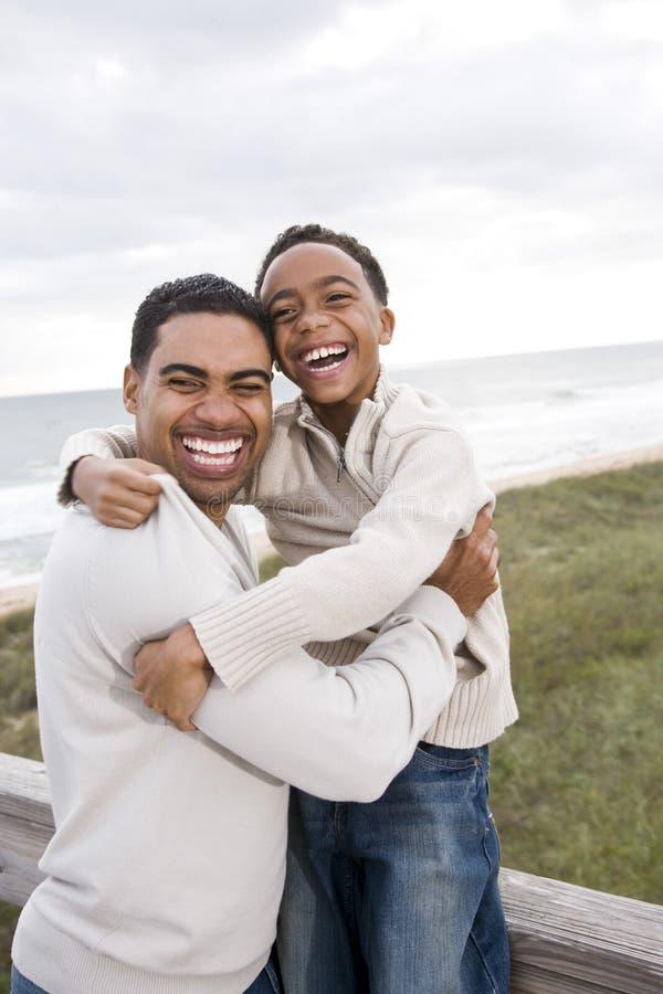 сынок отца пляжа афроамериканца смеясь над стоковые изображения rf