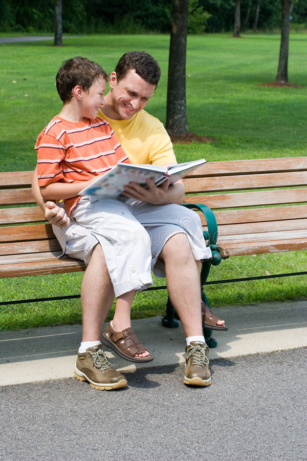 сынок чтения отца стоковое изображение