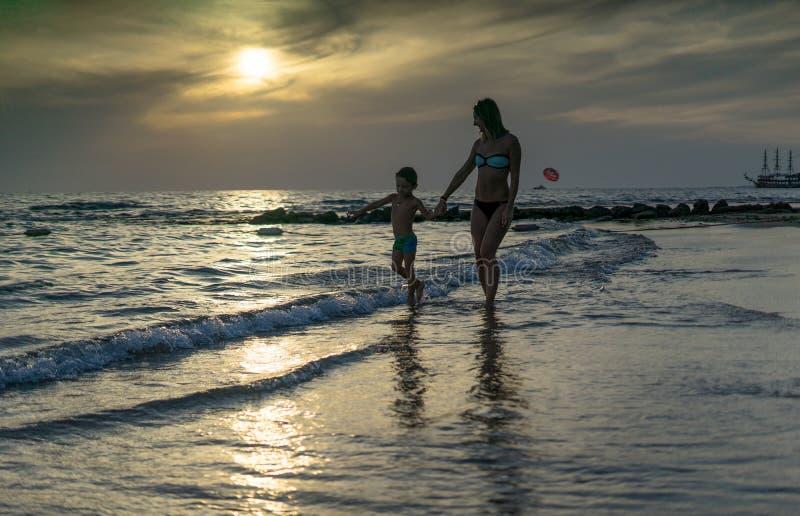 Сын молодого ребёнка матери и усмехаться играя на пляже на заходе солнца Положительные человеческие эмоции, чувства, утеха смешно стоковая фотография rf