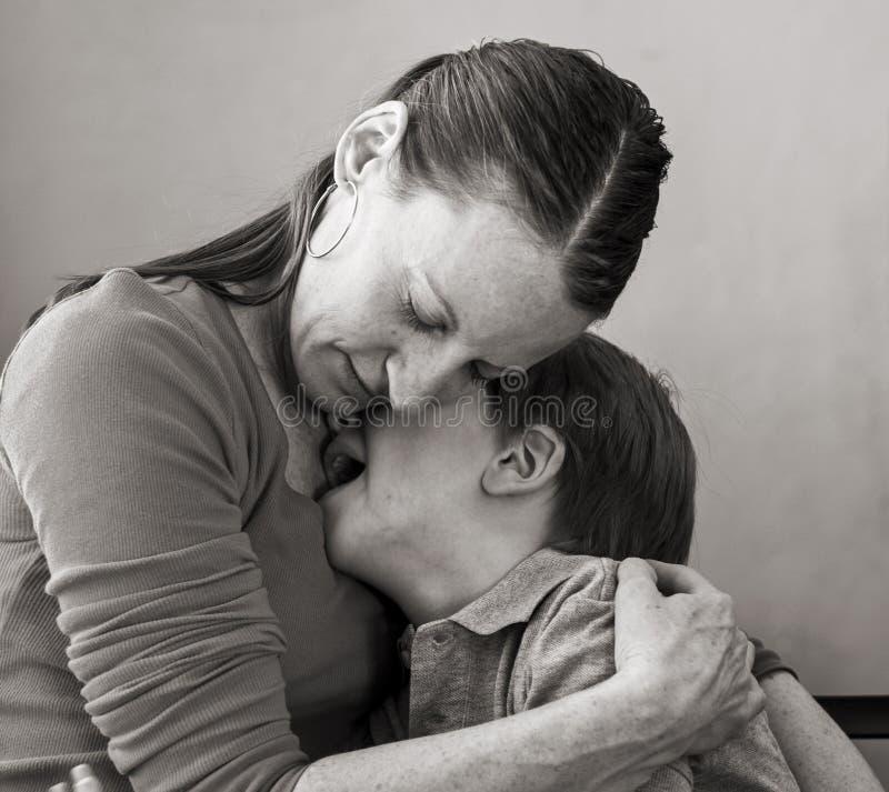 Сын объятий матери плача стоковое изображение
