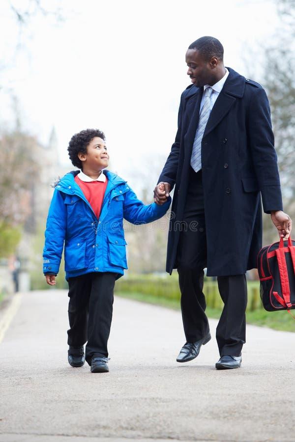 Сын отца идя к школе вдоль пути стоковое изображение rf