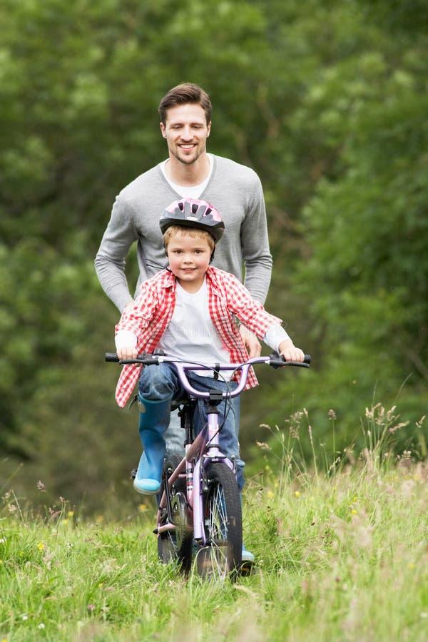 Сын отца уча для того чтобы ехать велосипед в сельской местности стоковое фото