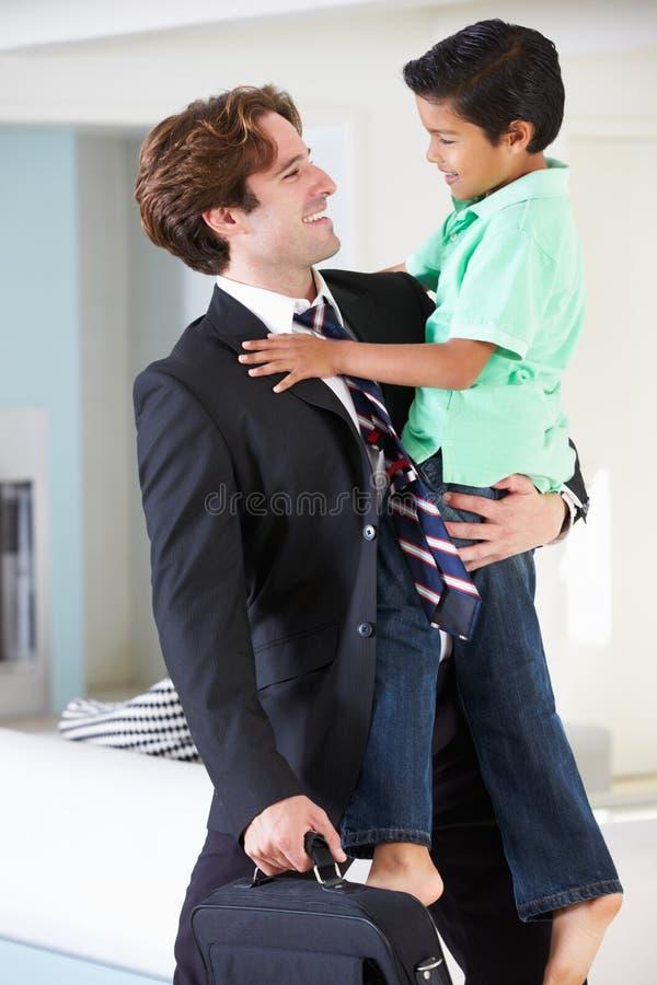 Сын приветствует отца на возвращении от работы стоковое фото rf