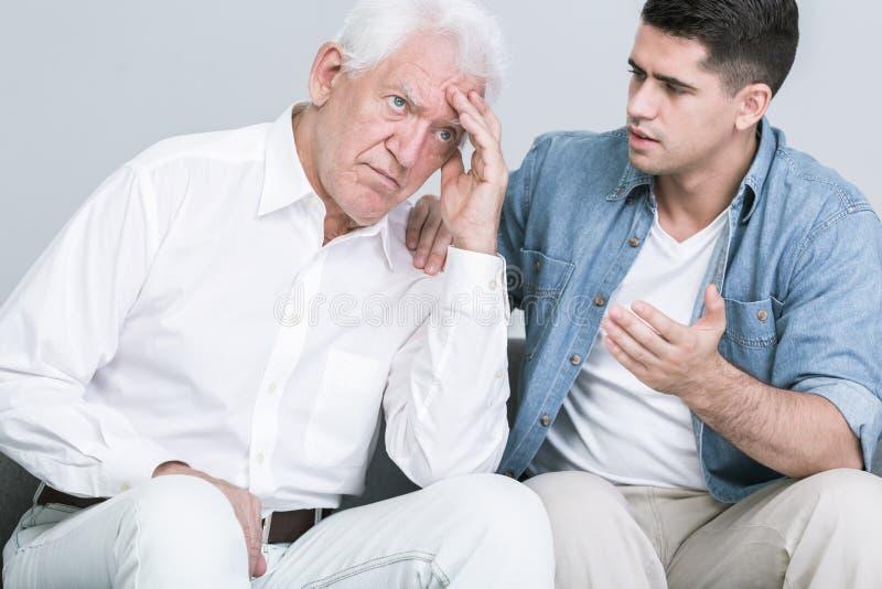 Сын разговаривая с потревоженным отцом стоковые фото