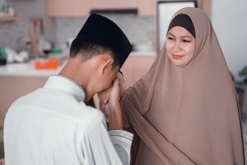 Сын целуя ее руку матери извиняется в eid mubarak стоковая фотография