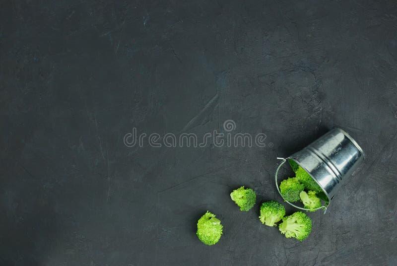 Сыпь брокколи здоровой еды свежая от ведра на черной предпосылке над взглядом скопируйте космос стоковое фото