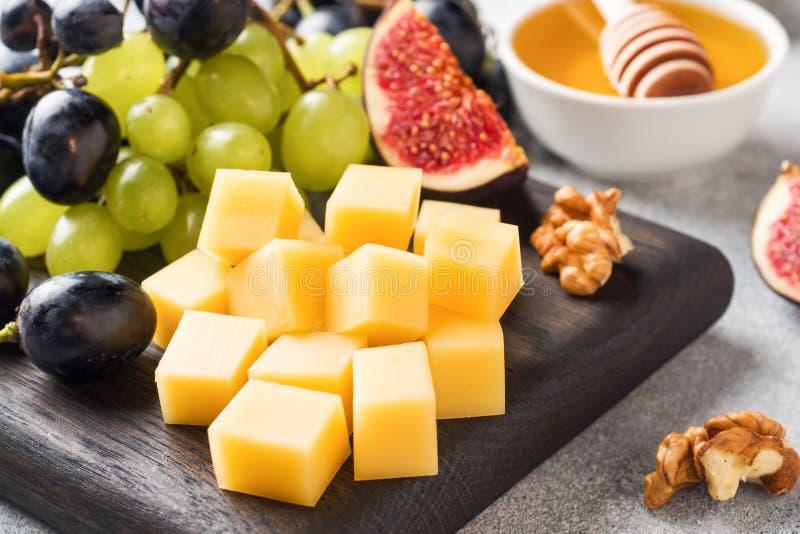 Сырные кубики, свежие фруктовые фиги винограда Медовый орех на деревянной рубке Селективная фокусировка Закрыть стоковая фотография rf