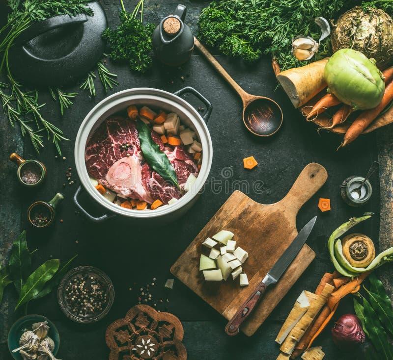 Сырое мясо в варить бак на предпосылке кухонного стола с овощами, приправой и утварями кухни, взглядом сверху r Мясо стоковые изображения
