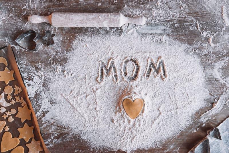 Сырое сердце сформировало печенье и маму слова написанные в муке, концепции дня матерей стоковое фото rf