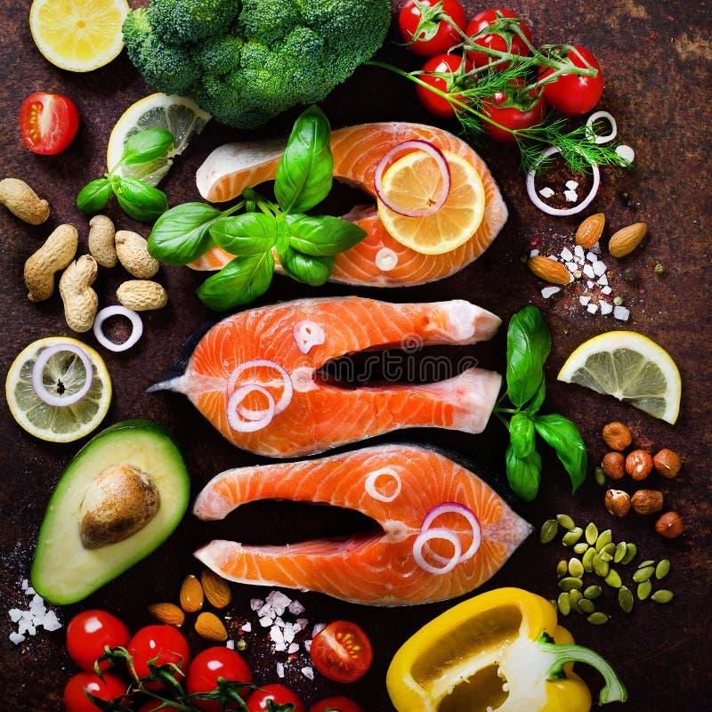 Сырое salmon филе рыб с ароматичными травами, лук, авокадо, брокколи, колокол перца, овощи на деревянной предпосылке стоковые изображения rf