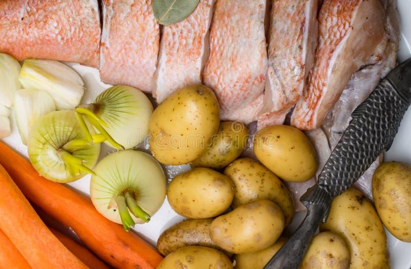 Сырой окунь моря, с специями рыб, морковь, картошки, перец, лук, лист залива, сельдерей на темной предпосылке Здоровая еда и диет стоковые фото