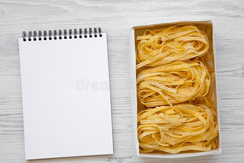 Сырой fettuccine макаронных изделий в бумажной коробке и пустом блокноте на белом деревянном столе, осматривает сверху Плоское по стоковое фото