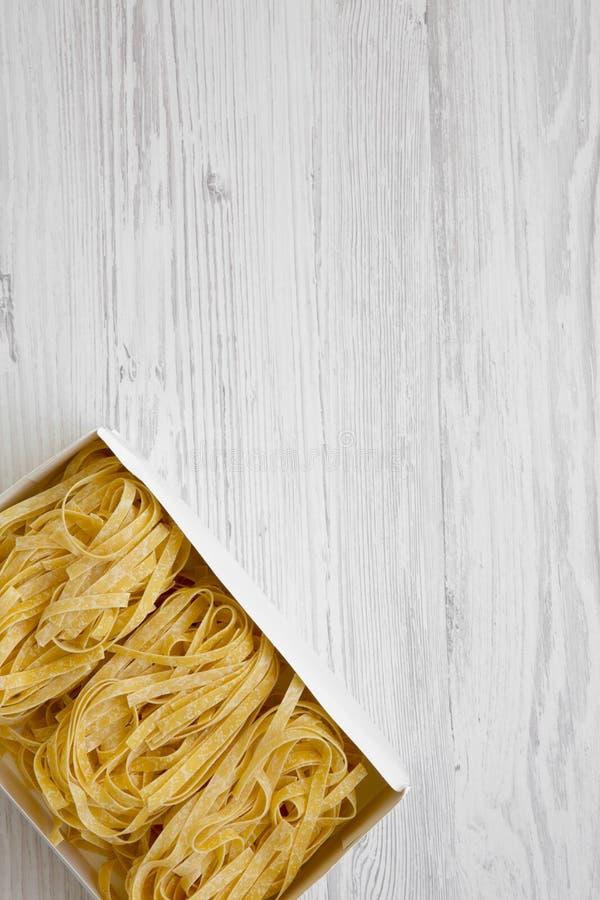 Сырой fettuccine макаронных изделий в бумажной коробке на белой деревянной предпосылке, осматривает сверху стоковые изображения