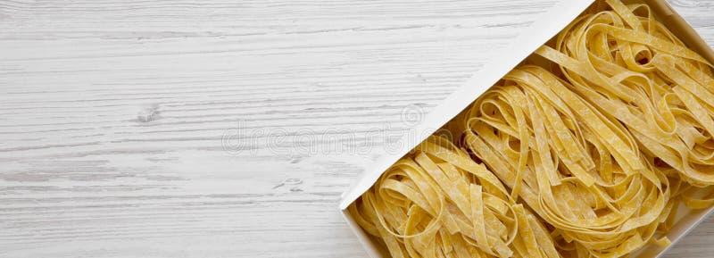 Сырой fettuccine макаронных изделий в коробке бумаги на белой деревянной поверхности, взгляде сверху Космос для текста стоковое фото rf