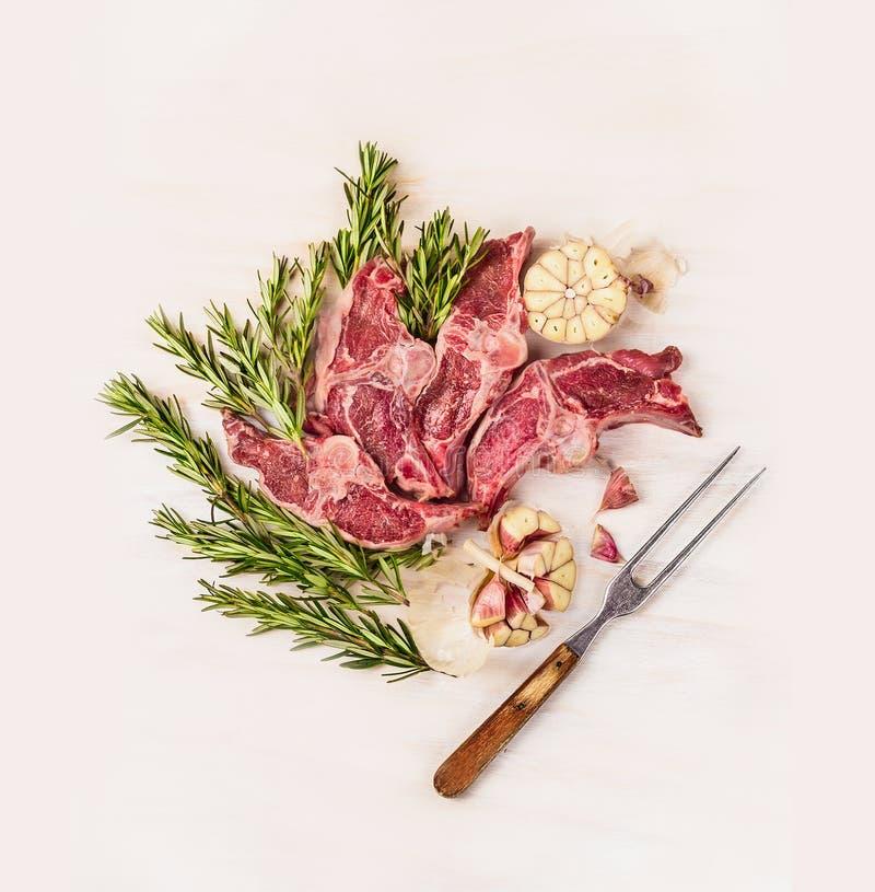 Сырцовая двойная поясница овечки прерывает с травой и специями вилки мяса на белой деревянной предпосылке стоковые фото