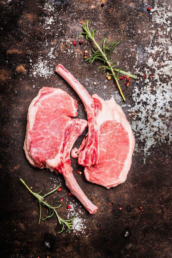Сырцовая свиная отбивная 2 с косточкой для жарить или жарить на ржавой предпосылке металла стоковое изображение