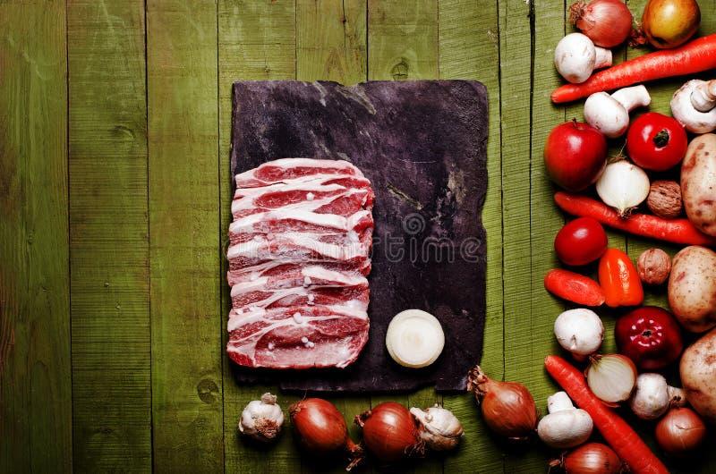 Сырцовое, который замерли мясо на зеленой деревянной предпосылке Шея сырцовая, veget свинины стоковое фото rf