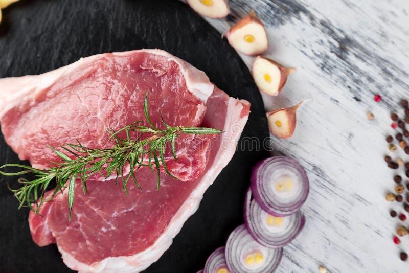 Сырцовое мясо свинины на черной плите шифера с ингридиентом специи стоковые изображения