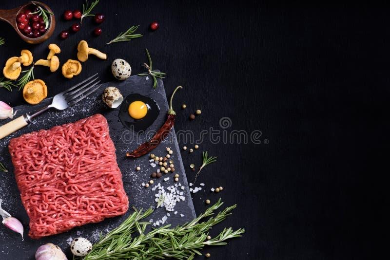 Сырцовое сочное земное мясо, подготавливает для жарить в духовке над голубым тонизированным взглядом инструментов стоковая фотография