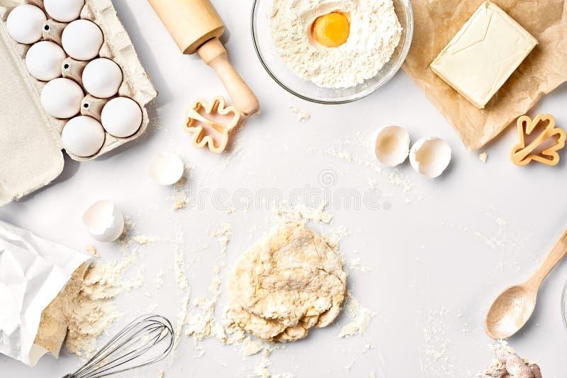 Сырцовое тесто готовое для замешивать на белой таблице Ингридиенты хлебопекарни, яичка, мука, масло Формы для делать печенья стоковое изображение