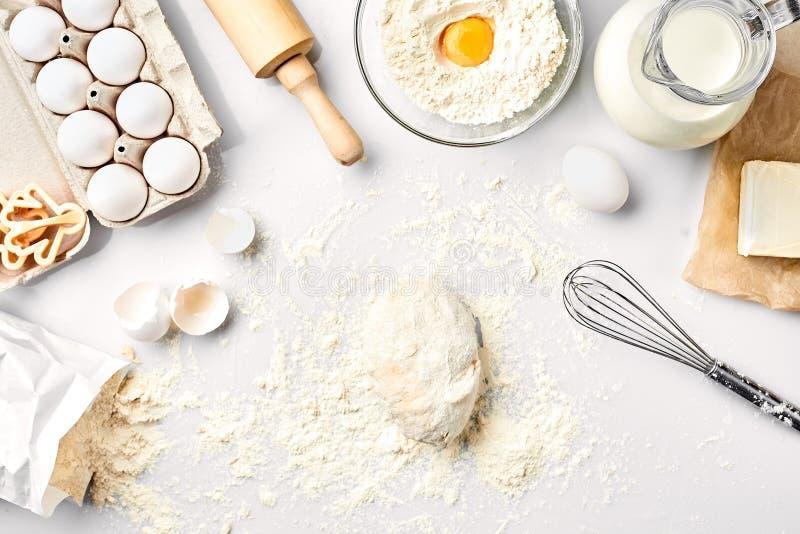 Сырцовое тесто готовое для замешивать на белой таблице Ингридиенты хлебопекарни, яичка, мука, масло Формы для делать печенья стоковые изображения