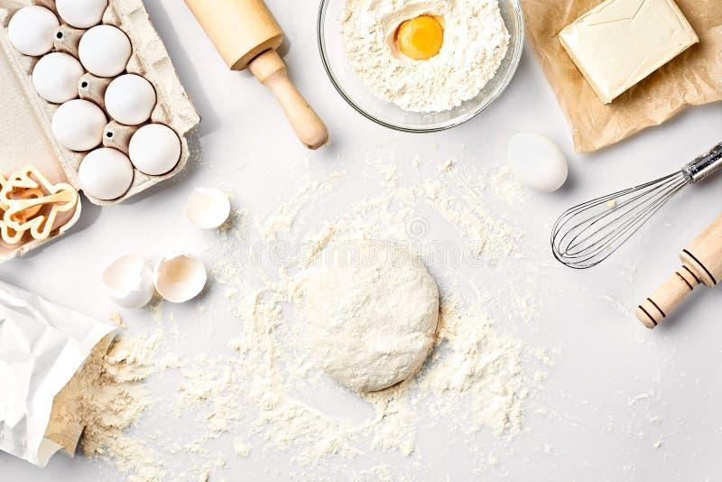 Сырцовое тесто готовое для замешивать на белой таблице Ингридиенты хлебопекарни, яичка, мука, масло Формы для делать печенья стоковое изображение rf