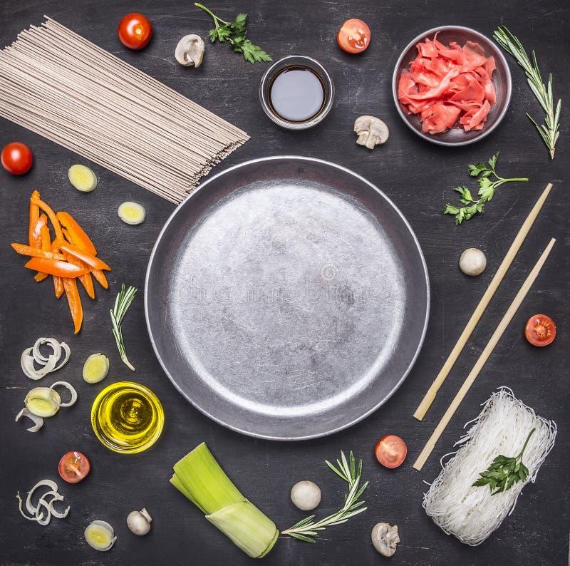 Сырцовые лапши гречихи с овощами, имбирем, палочками и ингридиентами, клали вне вокруг места лотка для текста, рамки на деревянно стоковое фото
