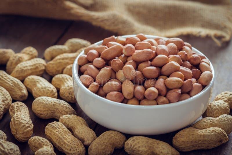 Сырцовые арахисы в белой раковине шара и арахиса на деревянном столе стоковое изображение rf