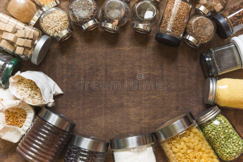 Сырцовые зерна, хлопья и макаронные изделия в стеклянных опарниках на деревянном столе o Dieting Balanced стоковая фотография rf