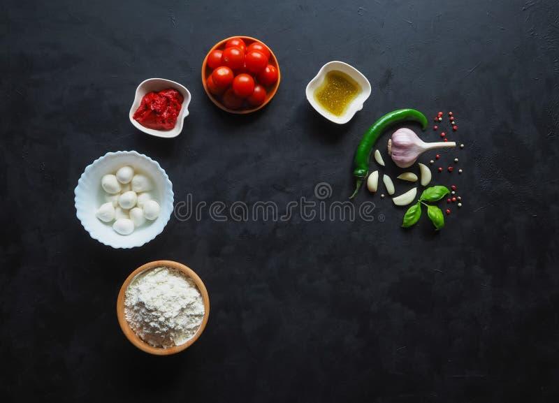Сырцовые ингридиенты margherita пиццы на доске с космосом экземпляра в центре стоковое фото