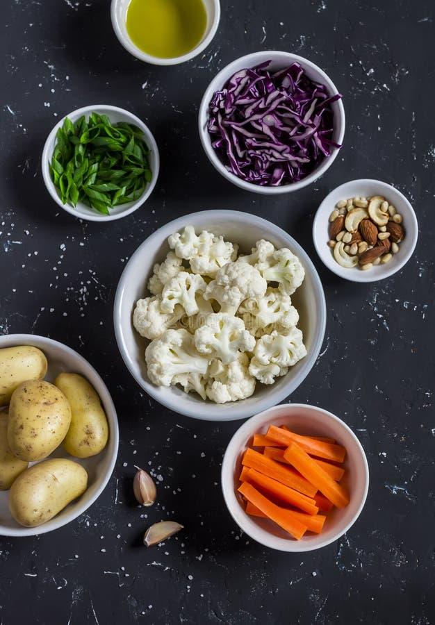 Сырцовые ингридиенты - картошки, цветная капуста и красная капуста, зеленые луки, моркови, гайки и оливковое масло в шарах на тем стоковые фотографии rf