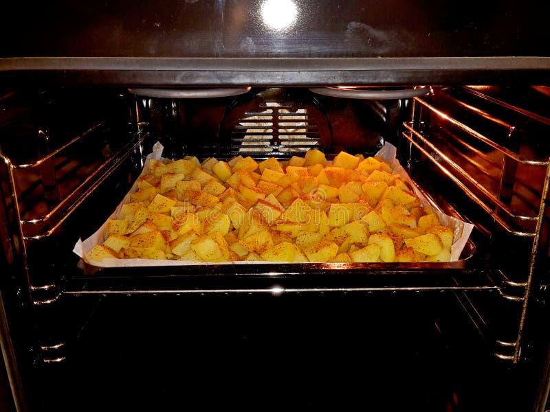 Сырцовые картошки подготовленные для жарить в духовке, spiced и помещенные на печь подносе и помещенные в печь печи стоковые изображения rf