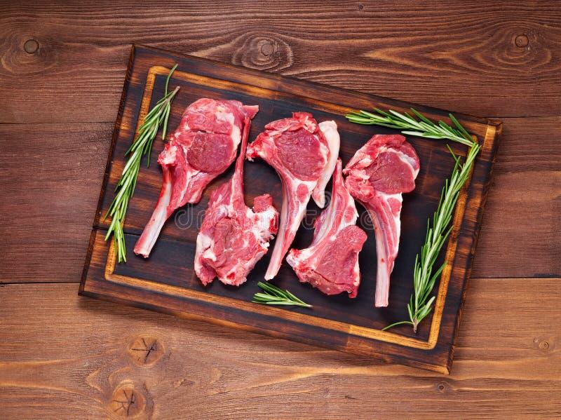 Сырцовые котлеты на косточке на предпосылке темного коричневого цвета деревянной, нервюры овечки овечки, взгляд сверху стоковая фотография