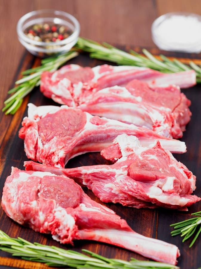 Сырцовые котлеты на косточке на предпосылке темного коричневого цвета деревянной, нервюры овечки овечки, взгляд со стороны, верти стоковые изображения