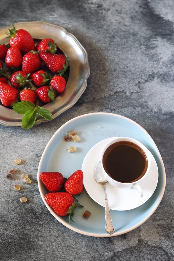 Сырцовые красные клубники и чашка черного кофе стоковые изображения