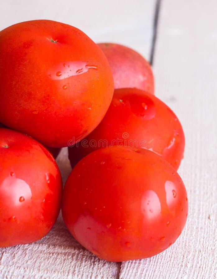 Сырцовые красные томаты на белой деревянной доске стоковые изображения