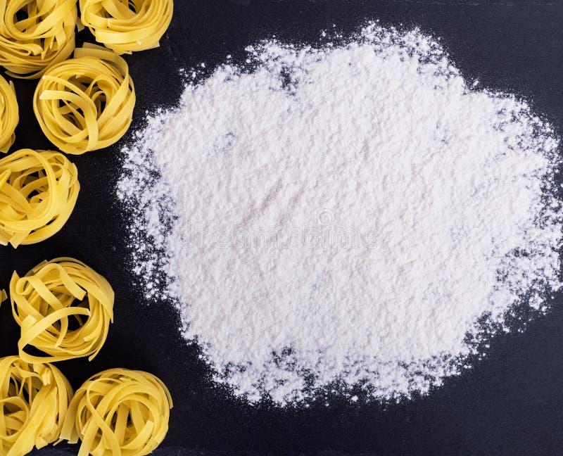 Сырцовые макаронные изделия и белая пшеничная мука стоковые изображения