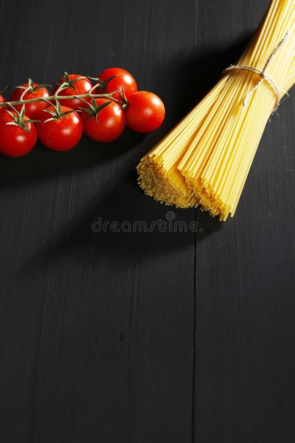 Сырцовые макаронные изделия и томаты на черной таблице стоковая фотография