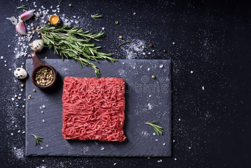 Сырцовые мраморизованные свежие семенят мясо и приправы на темной предпосылке стоковые фотографии rf