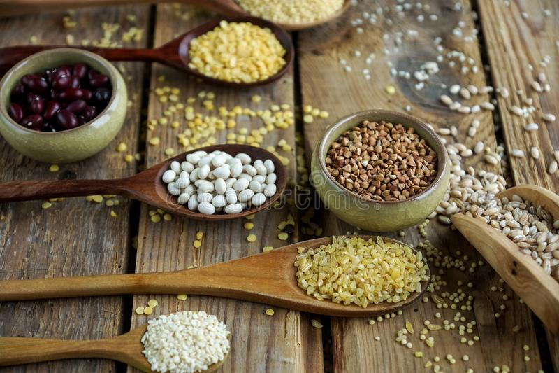 Сырцовые органические зерна, семена и фасоли хлопьев в деревянных ложках на деревенской деревянной предпосылке стоковая фотография