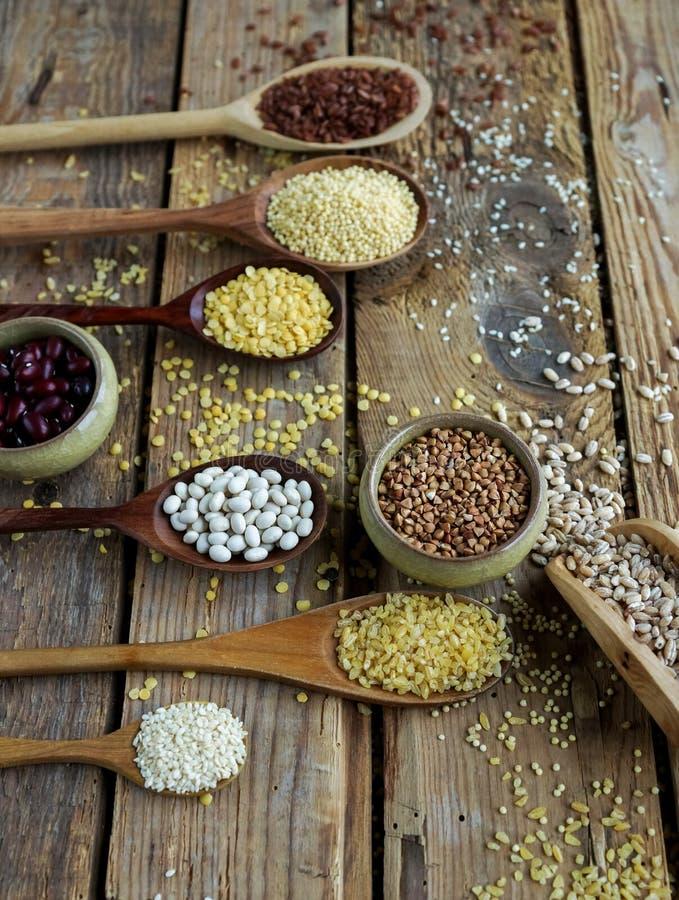 Сырцовые органические зерна, семена и фасоли хлопьев в деревянных ложках на деревенской деревянной предпосылке стоковые фото