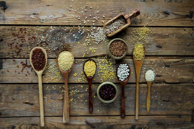 Сырцовые органические зерна, семена и фасоли хлопьев в деревянных ложках на деревенской деревянной предпосылке стоковое изображение