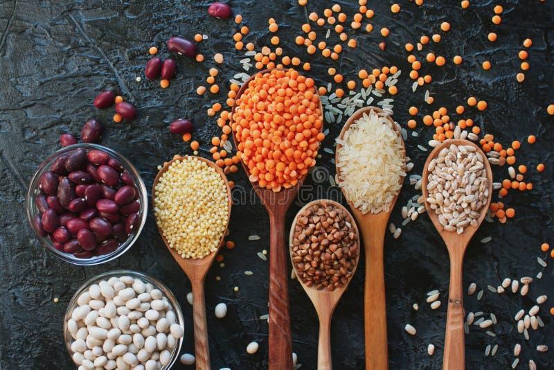 Сырцовые органические зерна, семена и фасоли хлопьев в деревянных ложках и шарах стоковые фото