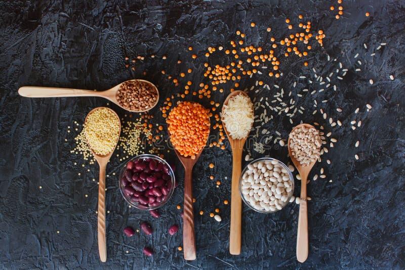 Сырцовые органические зерна, семена и фасоли хлопьев в деревянных ложках и шарах стоковая фотография