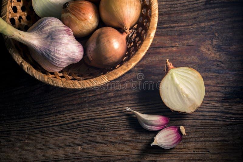 Сырцовые органические луки и чеснок на деревенской деревянной предпосылке r стоковая фотография rf